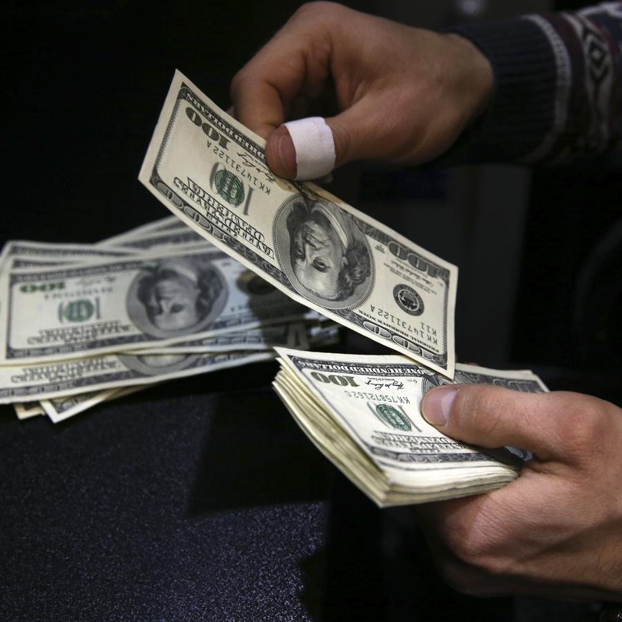 Hombre contando un fajo de billetes de dólares.
