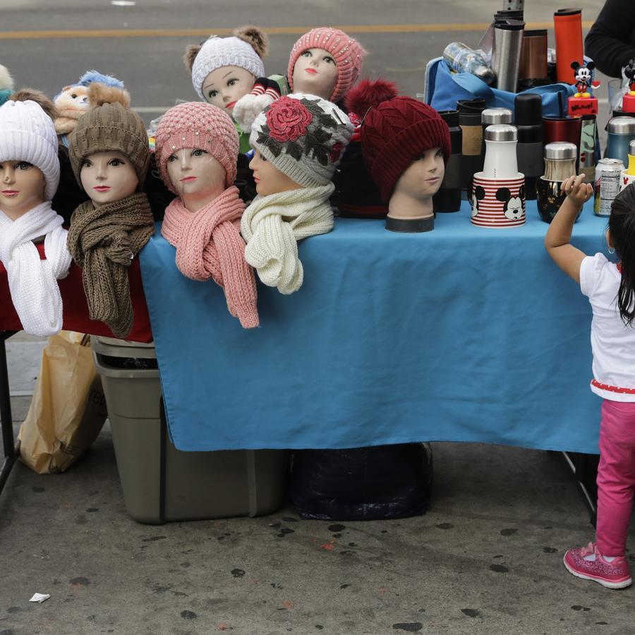 Las cabezas de maniquí con gorros y bufandas se colocan en una mesa mientras una niña mira productos en venta