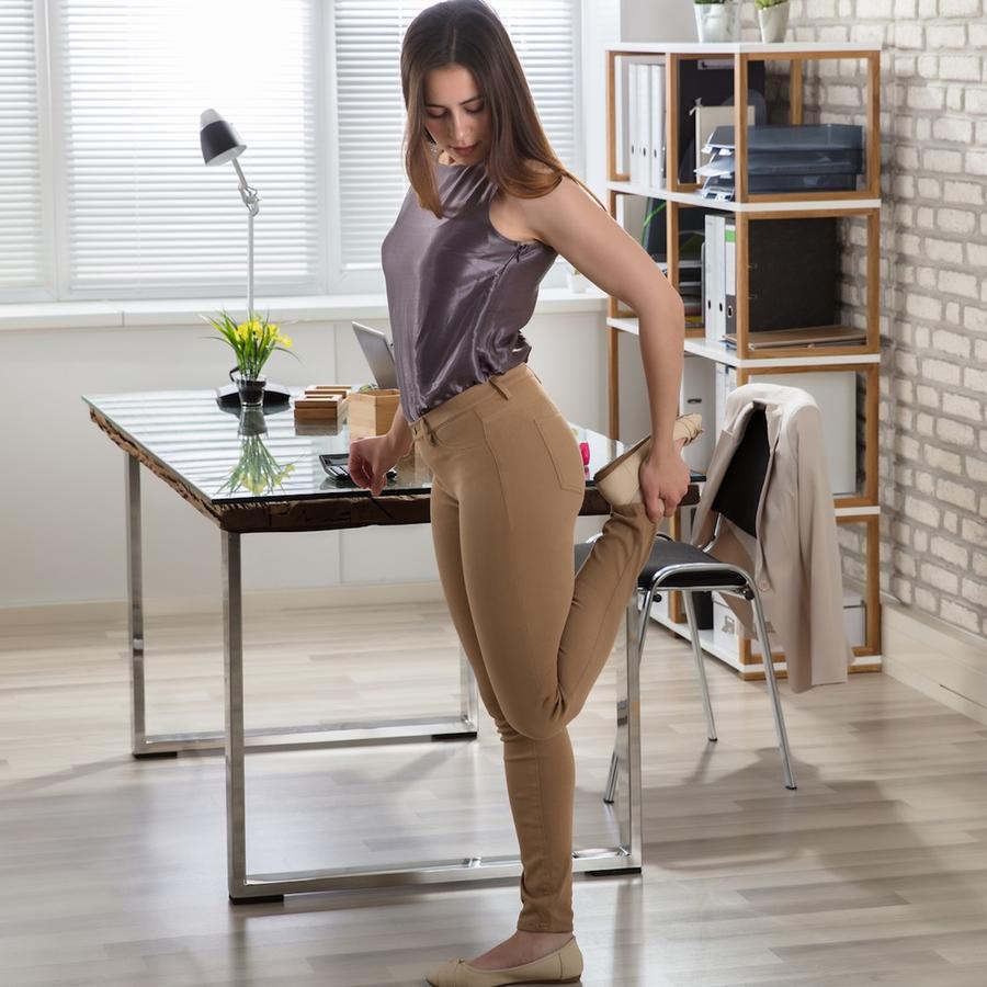 Mujer elongando en la oficina