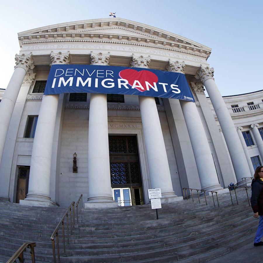 Un cartel en la entrada del edificio de la ciudad y el condado de Denver recibe a los inmigrantes indocumentados.