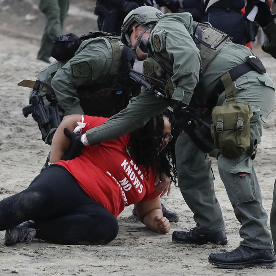Una mujer es detenida durante una protesta cerca de la frontera en Tijuana, México.