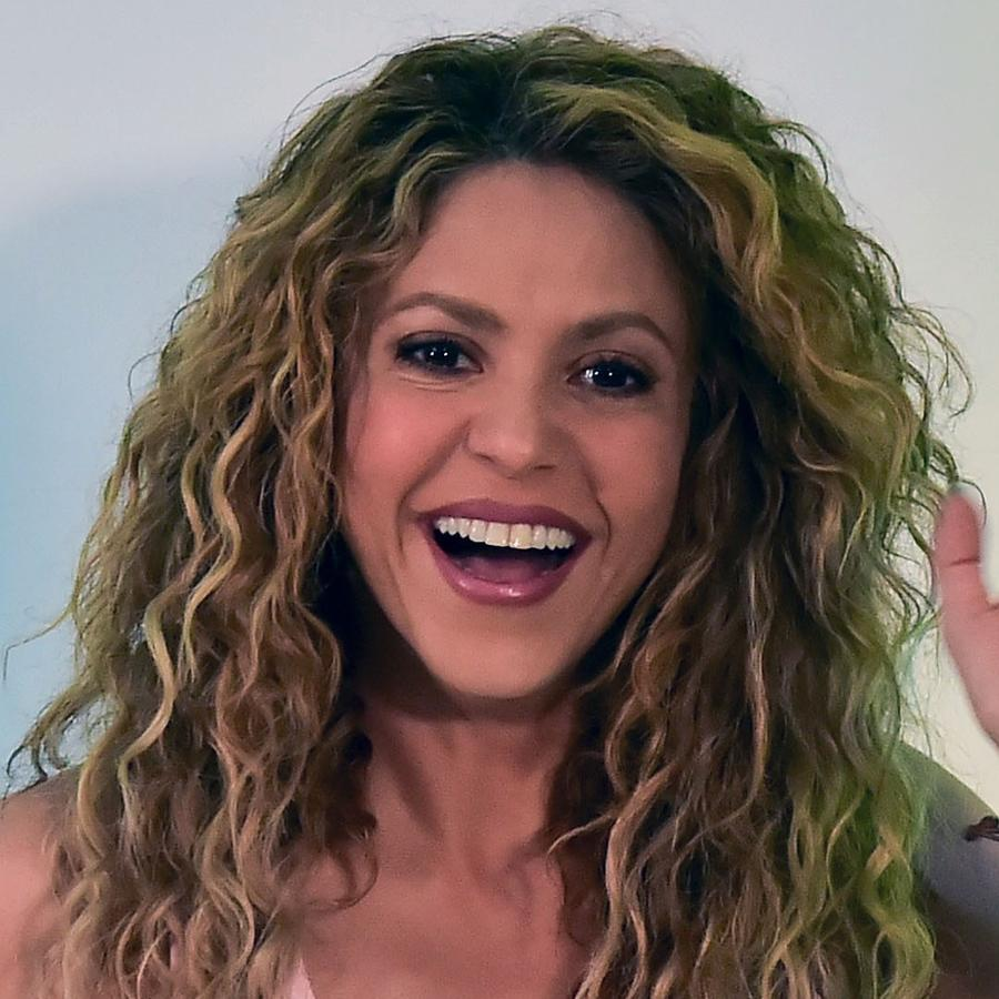 Shakira smiles and waves