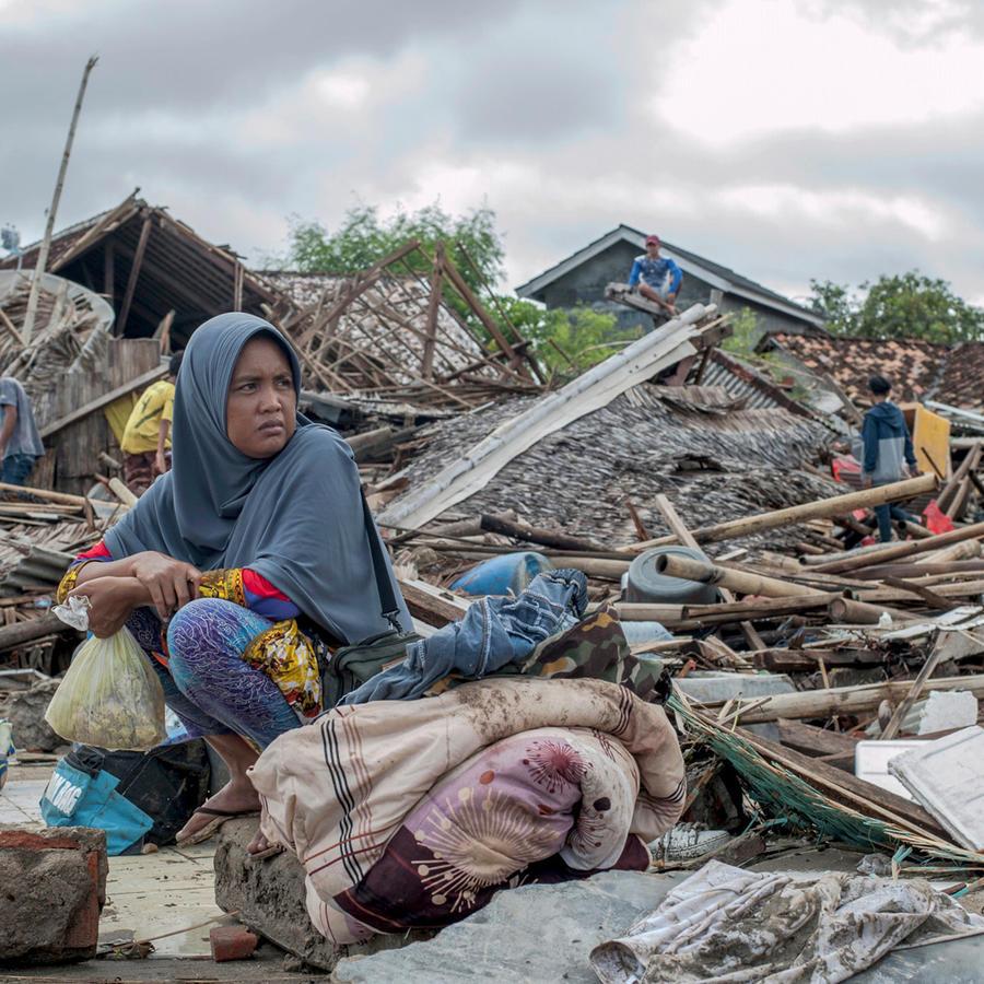 Una mujer sentada entre los escombros que dejó el tsunami en Indonesia
