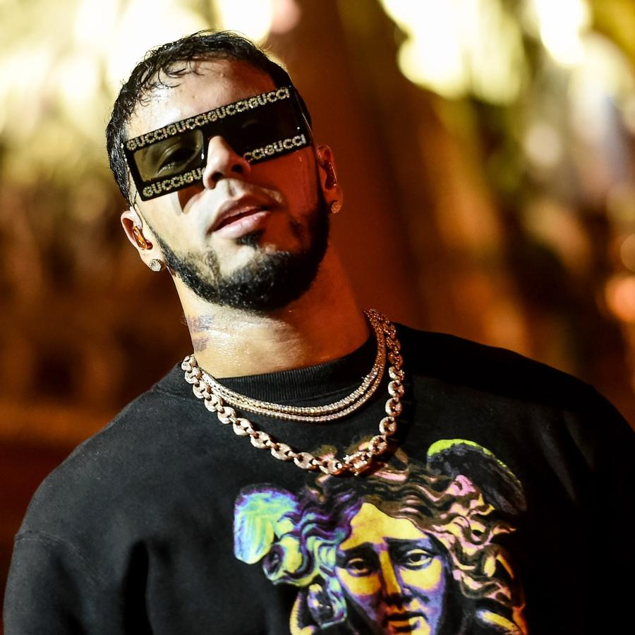 Anuel AA wears sunglasses during concert