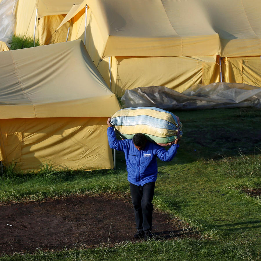 Venezuelan migrant carries his belongings out of a tent inside a temporary humanitarian camp that is closed by the government, in Bogota
