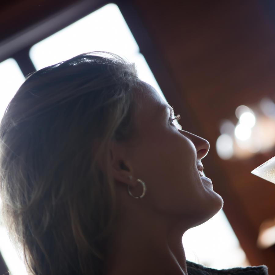 Chica bebiendo una copa de alcohol.