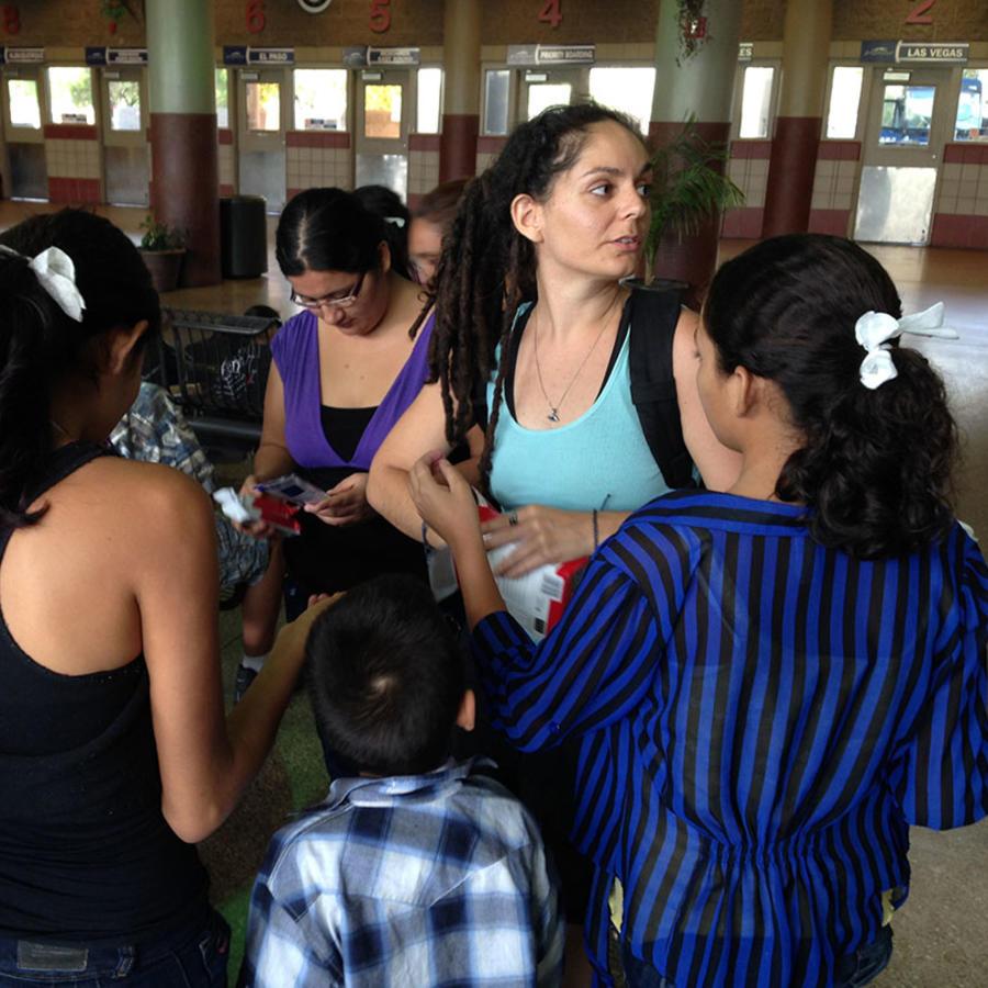 Una voluntaria del Phoenix Restoration Project reparte agua y comida a los migrantes que llegan a la estación de buses Greyhound en Arizona.