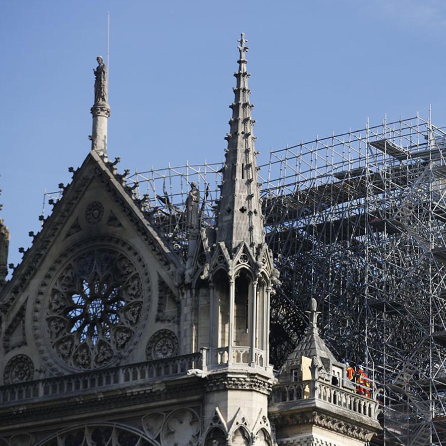 Varios bomberos revisan la catedral de Notre Dame tras el incendio que destruyó su aguja y redujo a cenizas el tejado.