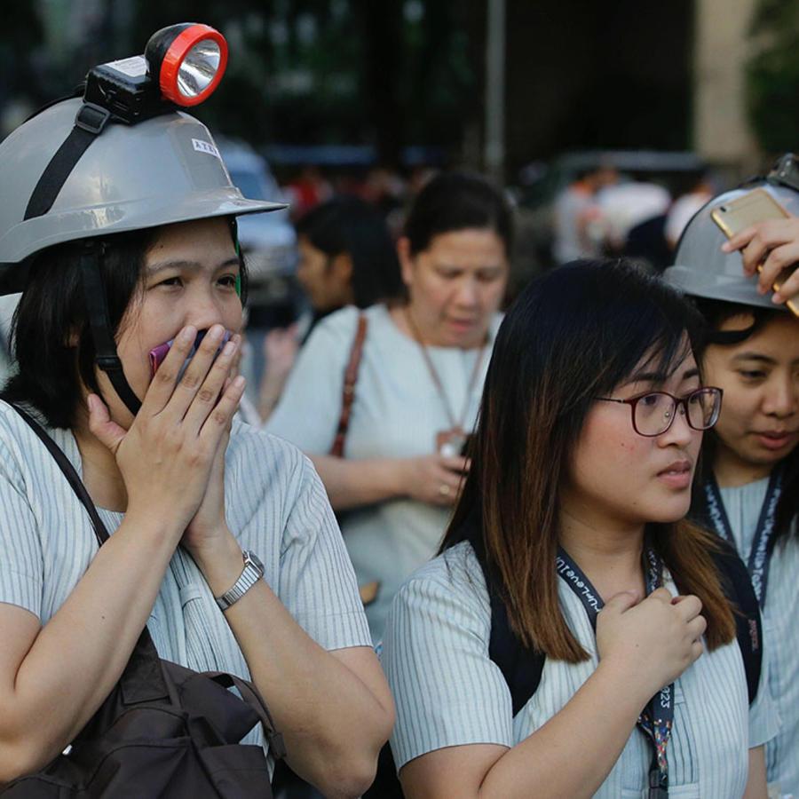 Varias personas usan cascos para protegerse de un potente sismo que estremeció Manila, capital de Filipinas.
