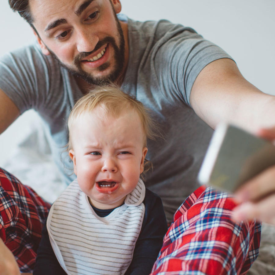 Papá tomando selfie a bebé llorando
