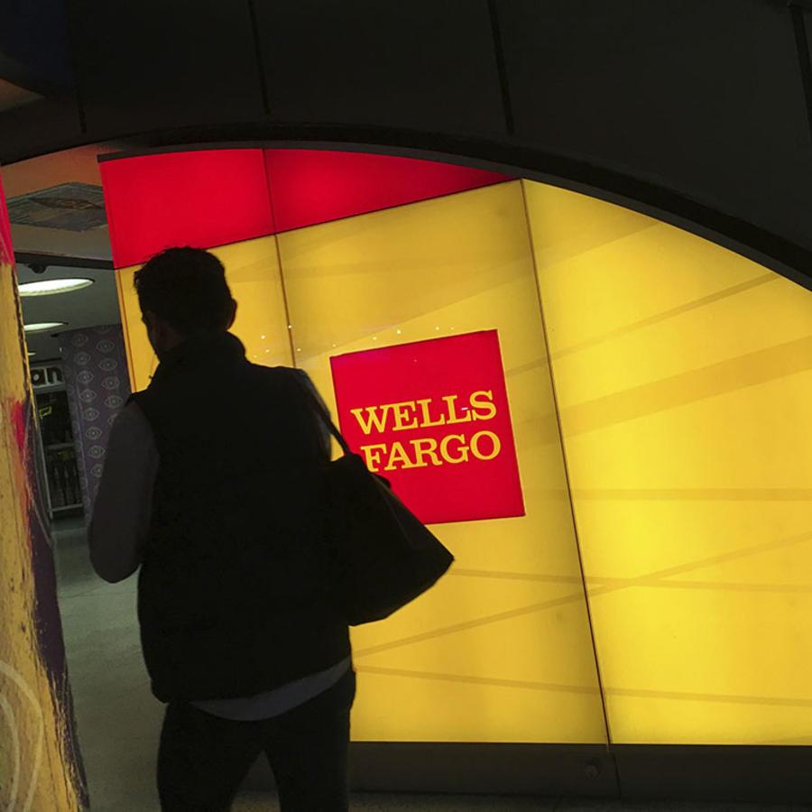 Un persona camina cerca de un cajero del banco Wells Fargo en Nueva York.