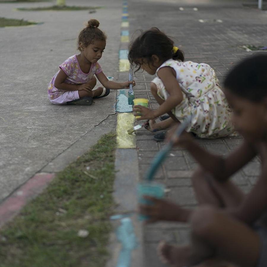 NIños brasileños dibujan sobre una calle de Río de Janeiro.