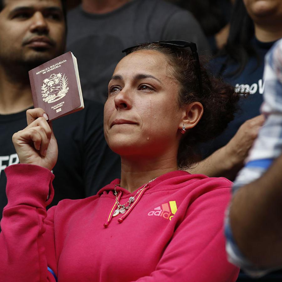 Una mujer sostiene en su mano un pasaporte de Venezuela mientras llora en las afueras de la embajada del país en Washington.