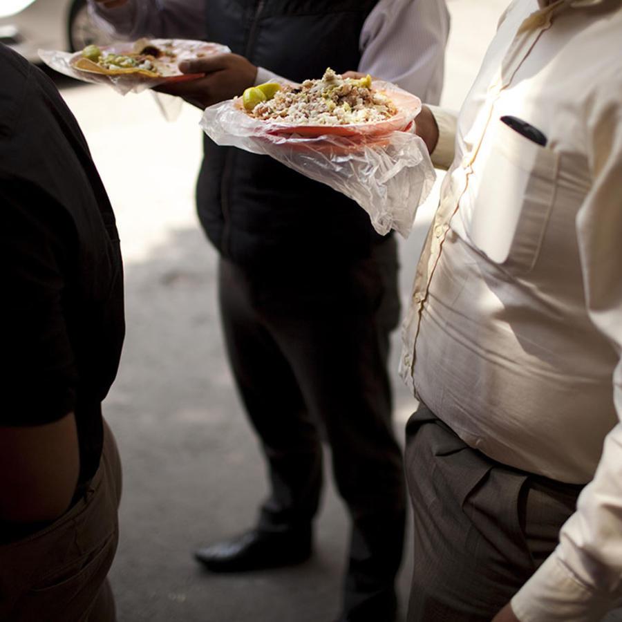Varios trabajadores comen tacos en la Ciudad de México durante su hora de almuerzo.