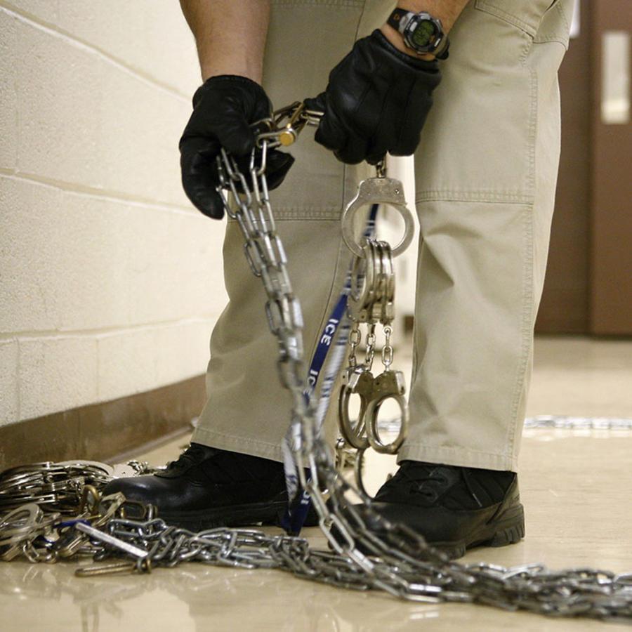 Un oficial de ICE revisa una esposas que utilizará para transferir a un inmigrante detenido.