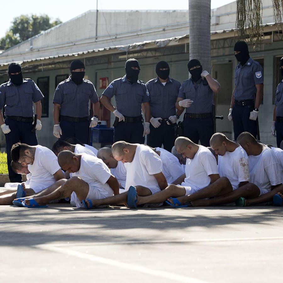 Pandilleros identificados por las autoridades salvadoreñas permanecen esposados en el piso.