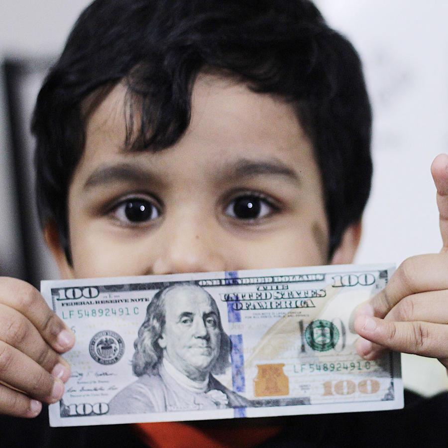 Niño mostrando un billete