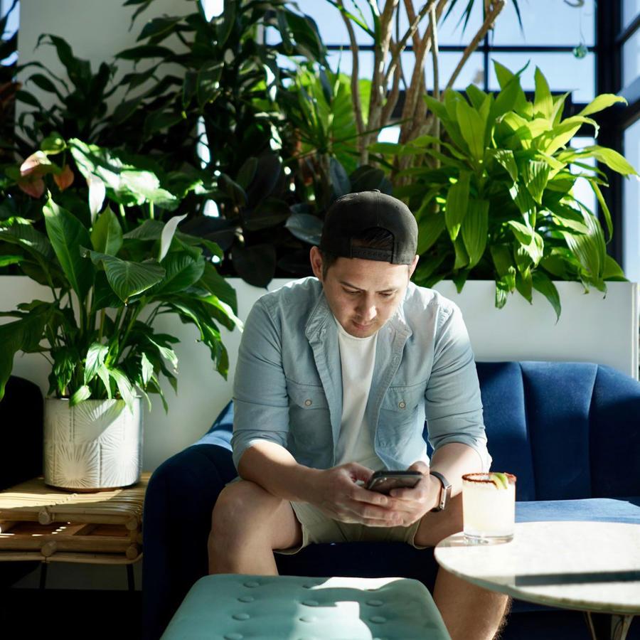 Joven usando teléfono en casa moderna