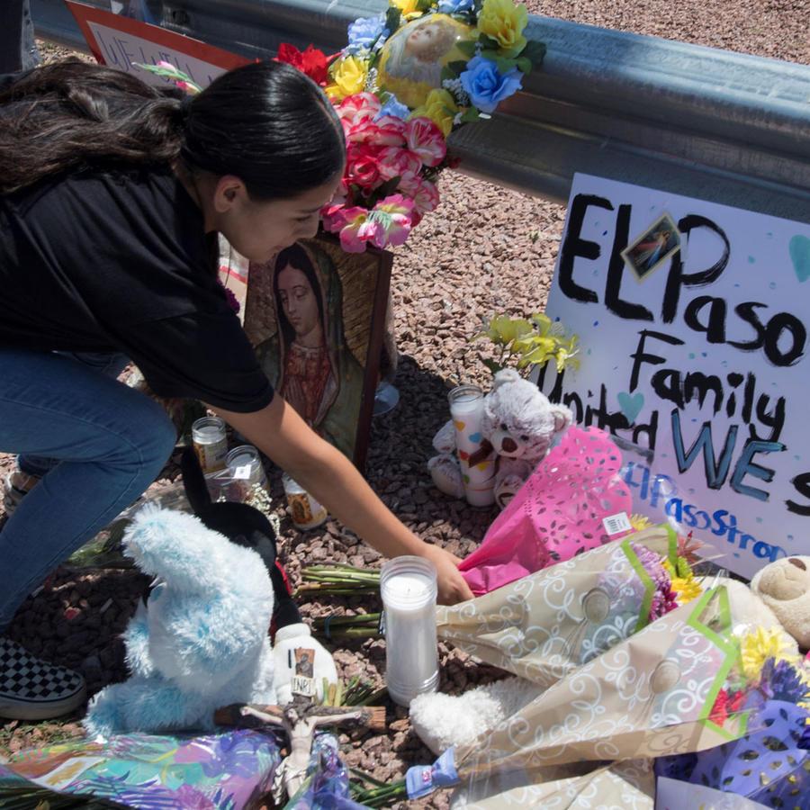 Mujer deja flores en memoria de los muertos en El Paso
