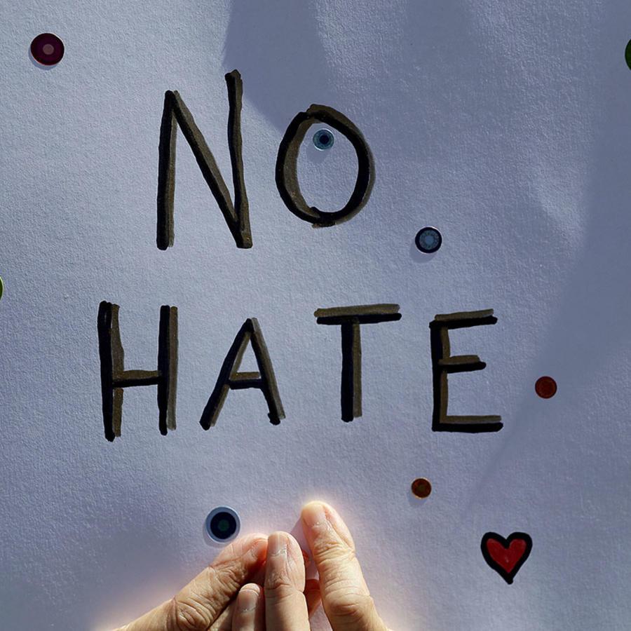 """Una persona sostiene un cartel que dice """"sin odio""""."""
