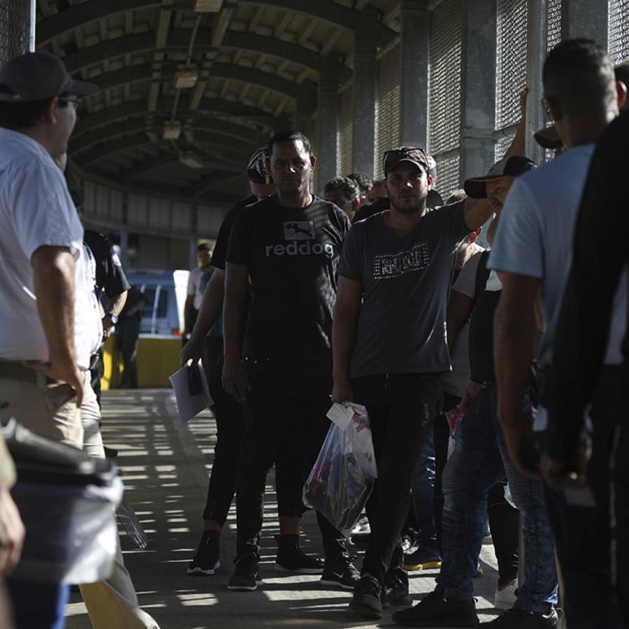 Migrantes esperan en una fila pararegresar a México y esperar sus turnos para solicitar asilo en Estados Unidos.