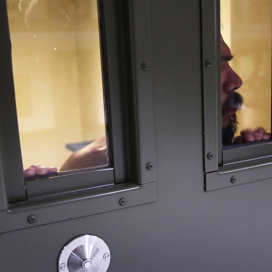 Un detenido inmigrante mira desde su 'celda de segregación' en el centro de detención de Adelanto el 15 de noviembre de 2013 en Adelanto, California.