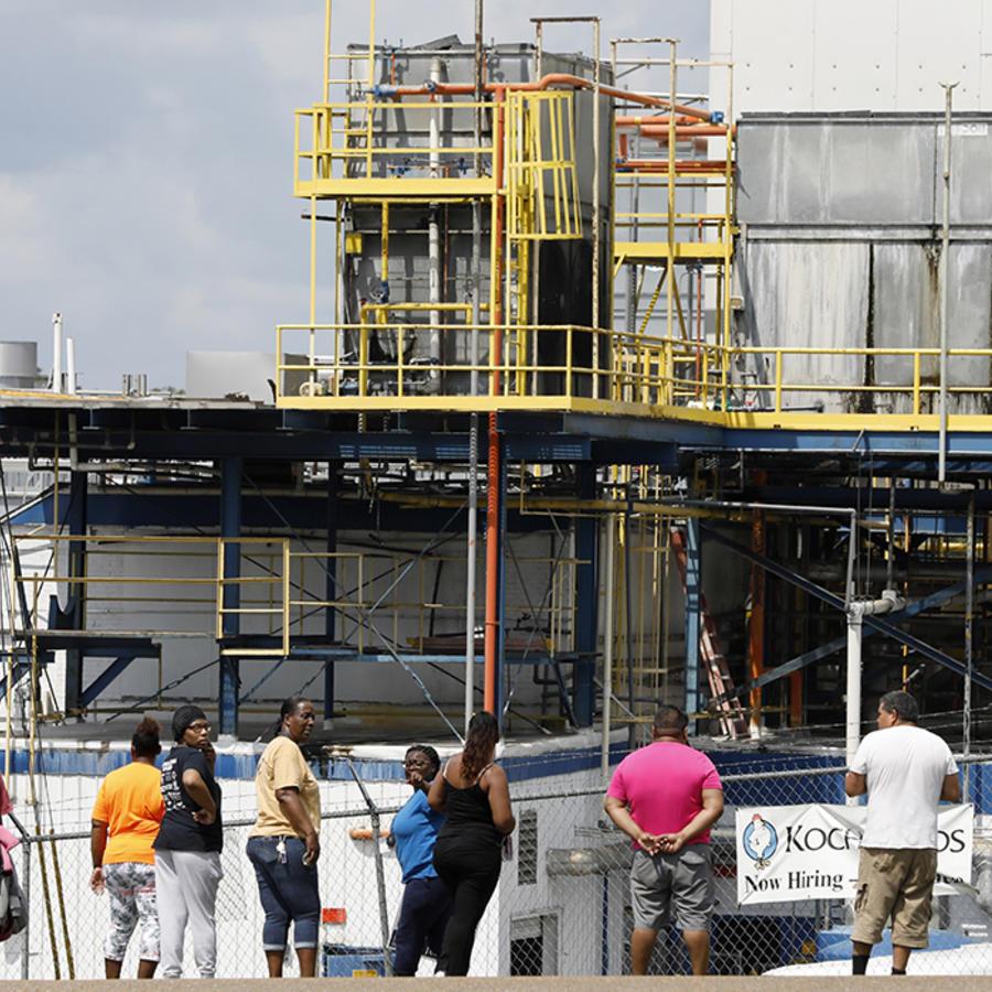 Varias personas esperan en las afueas de la fábrica de procesamiento de aves Koch Foods Inc, en Mississippi.