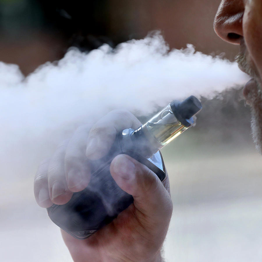 Una persona exhala mientras fuma un cigarrillo electrónico.