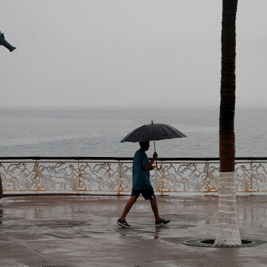 Un hombre camina bajo la fuerte lluvia provocada por la tormenta Lorena a su paso en el estado de Jalisco, México.