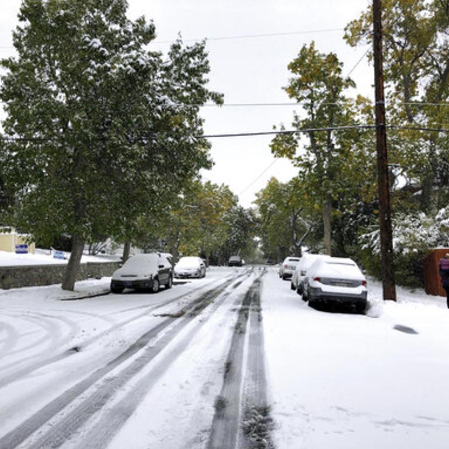 Peatones intentan abrirse paso este domingo por una calle de Helena, Montana, cubierta de nieve.