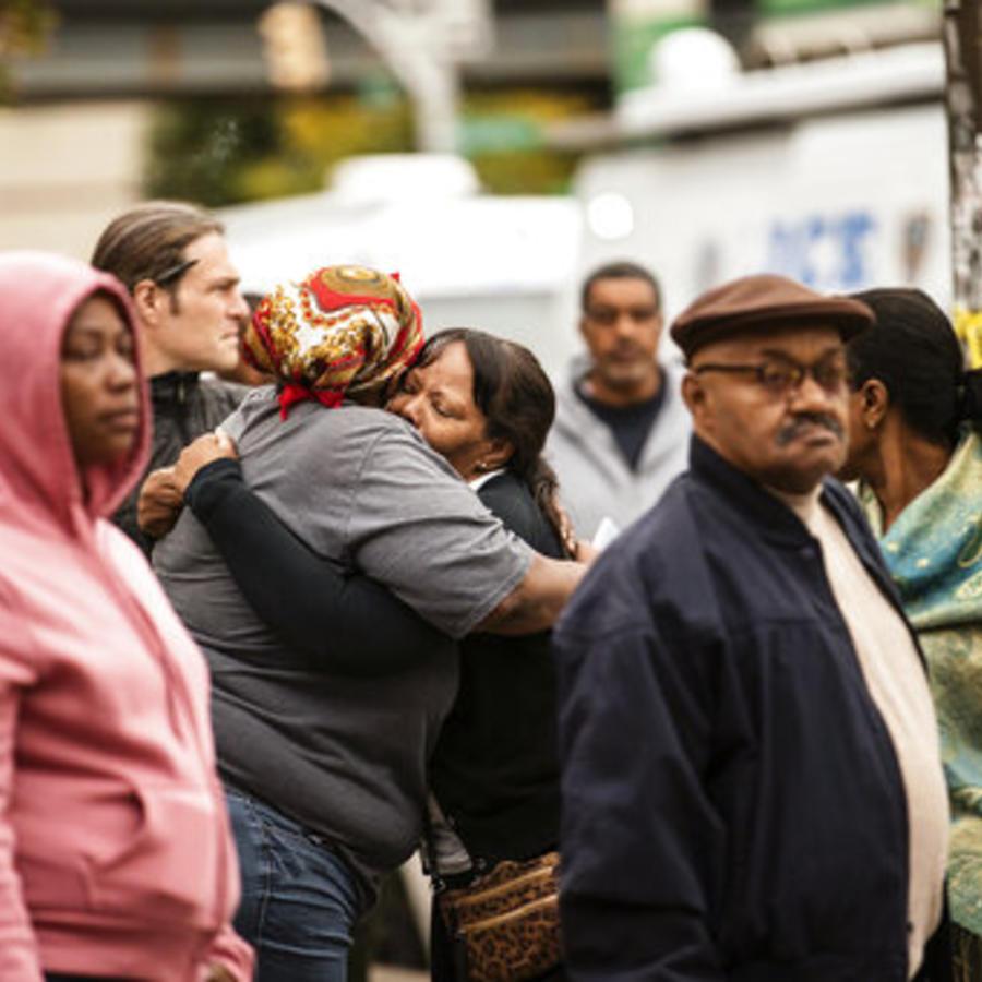 Dos personas se abrazan en el lugar donde un tiroteo dejó este sábado a cuatro muertos y tres heridos en Brookly, Nueva York.