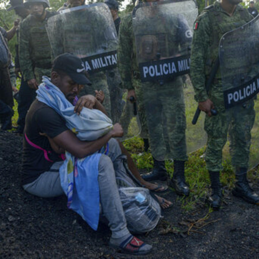 Un migrante con un niño pequeño rodeado por agentes de la Guardia Nacional este sábado en Chiapas, México.