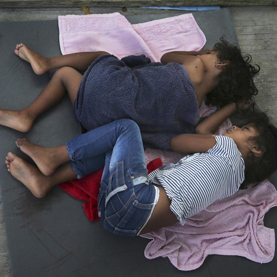 Dos niñas migrantes duermen sobre una lona en un albergue en Nuevo Laredo, México.