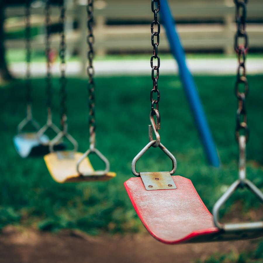 Varias sillas de columpio en un parque público.