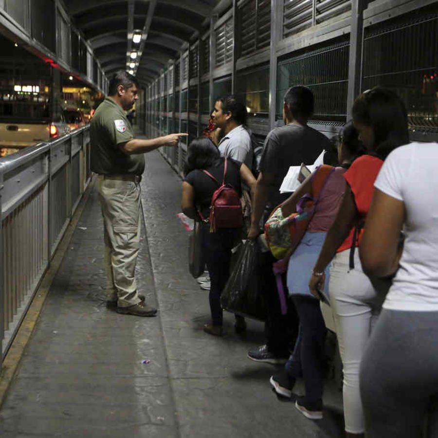 Un agente migratorio mexicano da instrucciones a migrantes que están solicitando asilo en Estados Unidos mientras aguardan en el Puente Internacional 1 en Nuevo Laredo, México, para ingresar a Laredo, Texas.