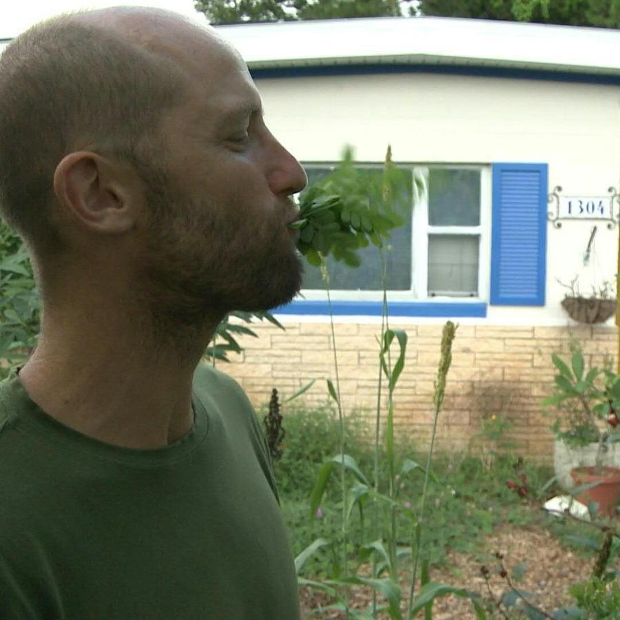 Rob Greenfield comiendo uno de los vegetales que él mismo produce en su patio en Orlando.