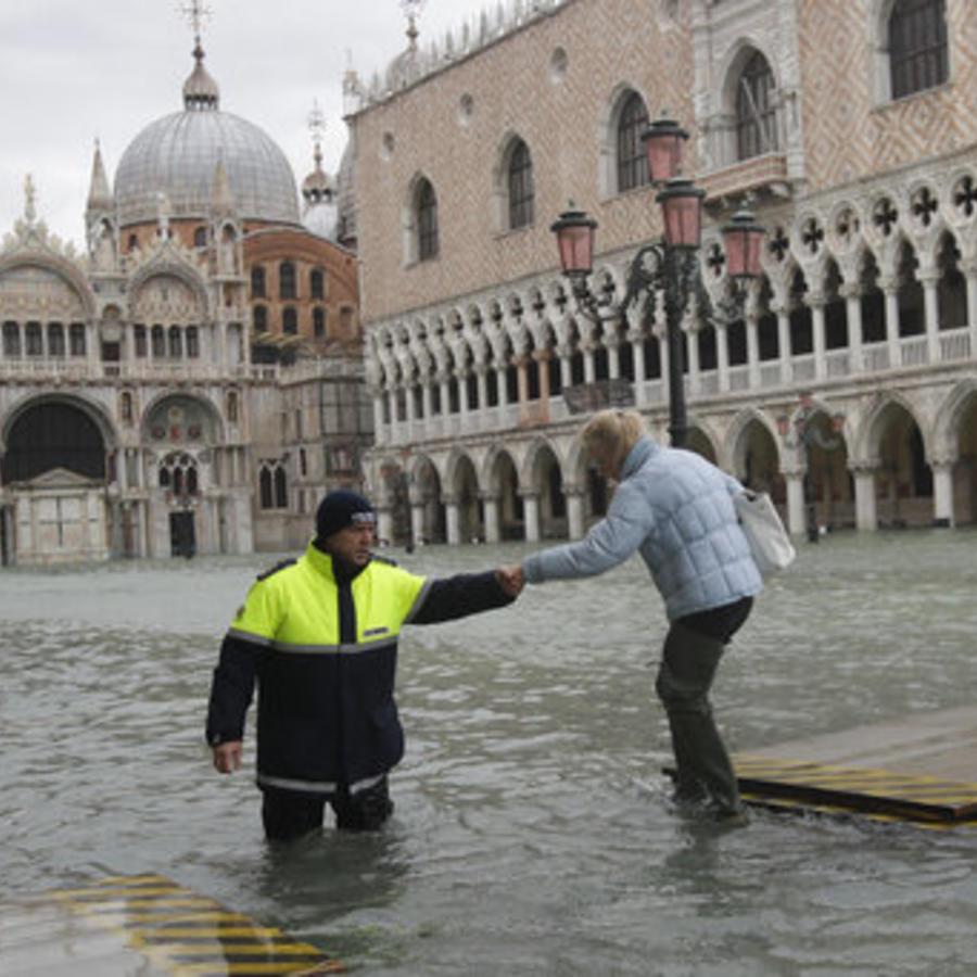 Un operador municipal socorre a una mujer que intentó cruzar este domingo la Plaza San Marcos de Venecia, cerrada por inundación.