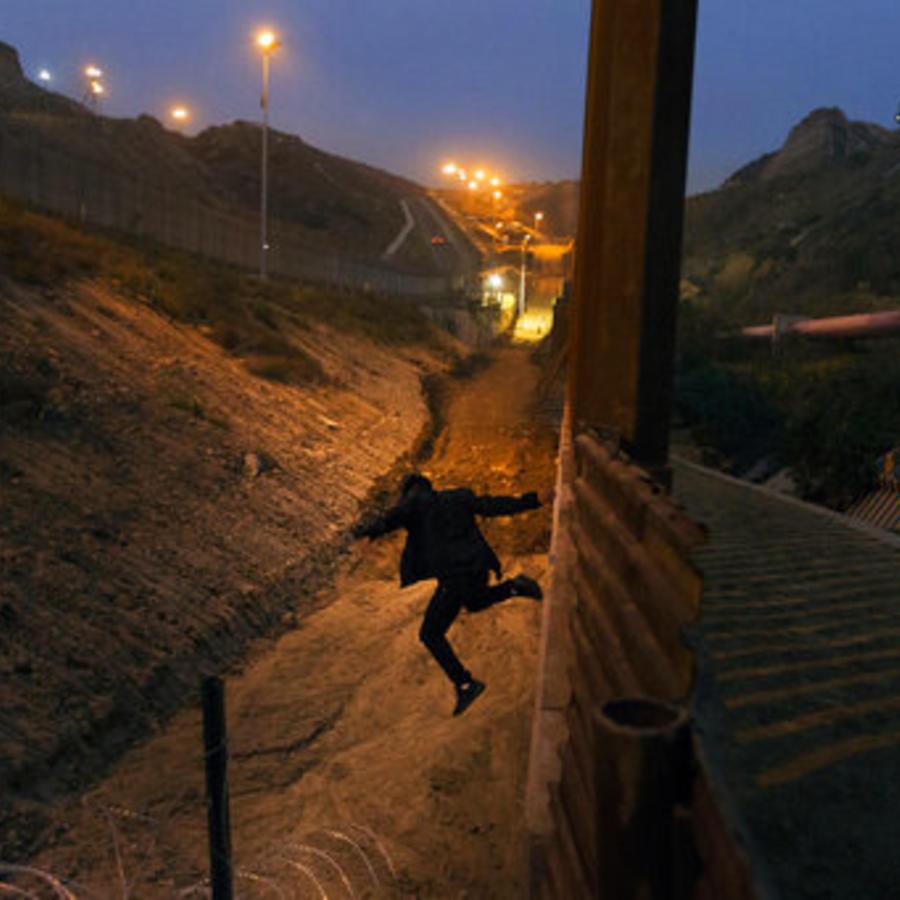 En esta foto de archivo del 21 de diciembre de 2018, un joven hondureño salta desde la valla fronteriza de Estados Unidos en Tijuana, México.