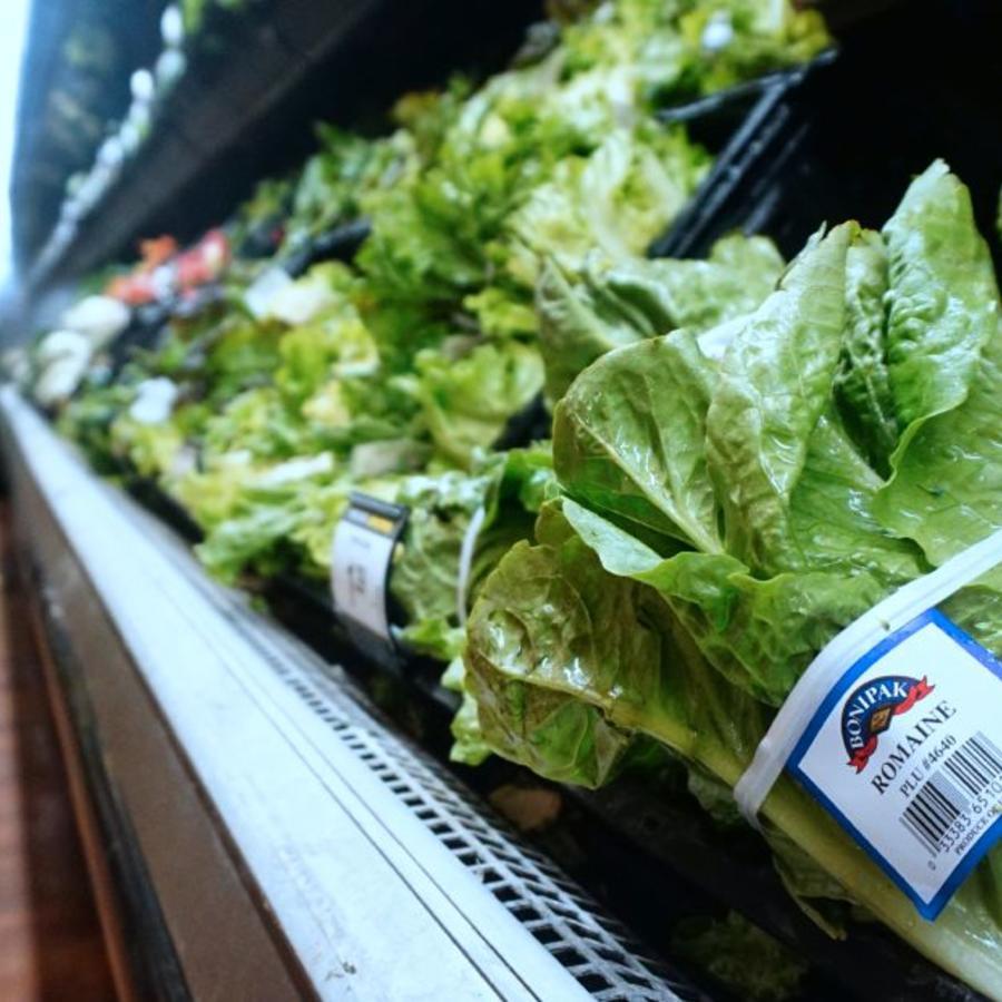 Un hombre compra verduras al lado de lechuga romana almacenada y a la venta en un supermercado en Los Ángeles, California