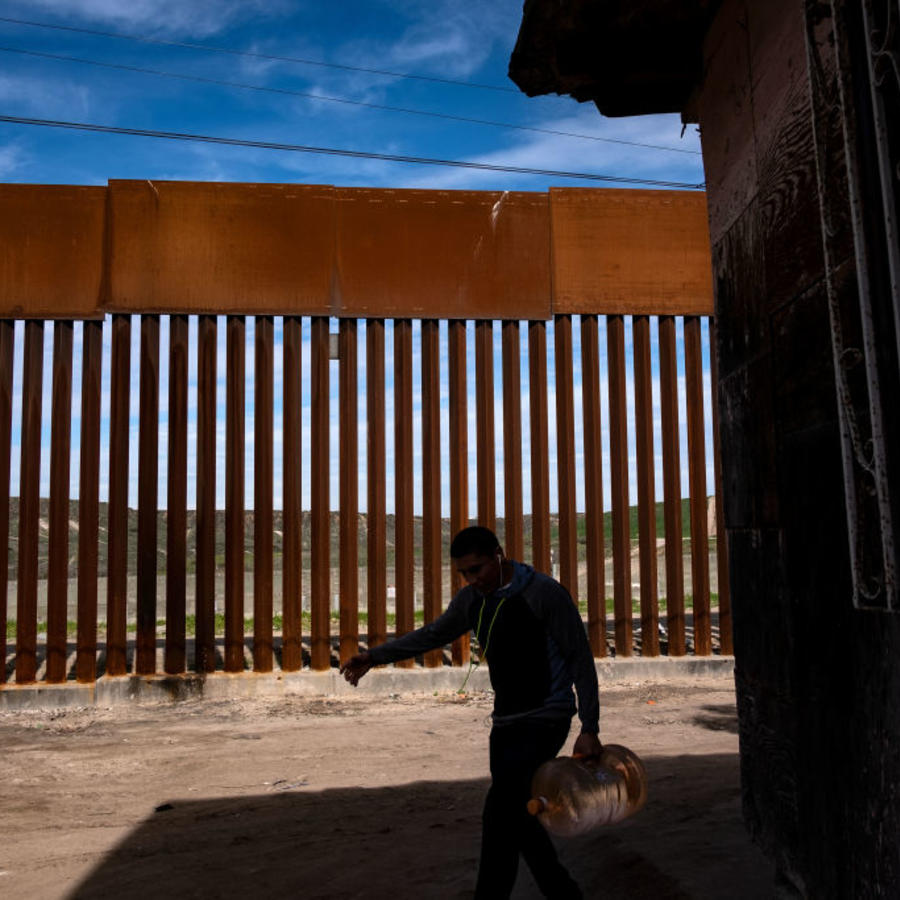 Un hombre transporta agua cerca de la valla fronteriza México-Estados Unidos en Tijuana, Estado de Baja California, México, el 28 de enero de 2019.