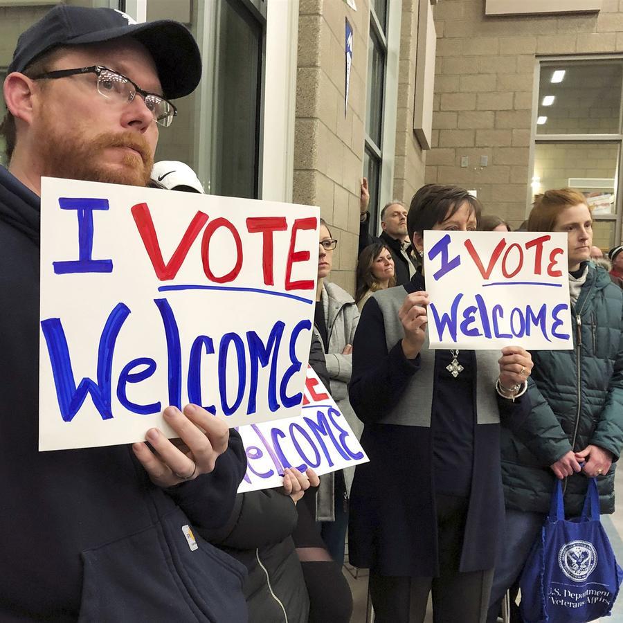 Los residentes que apoyan el continuo reasentamiento de refugiados sostienen carteles en una reunión en Bismarck, Dakota del Norte, el 9 de diciembre de 2019.James MacPherson / AP