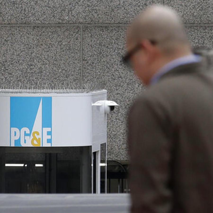 Un hombre cruza una calle en frente a un edificio de PG&E en San Francisco, California.