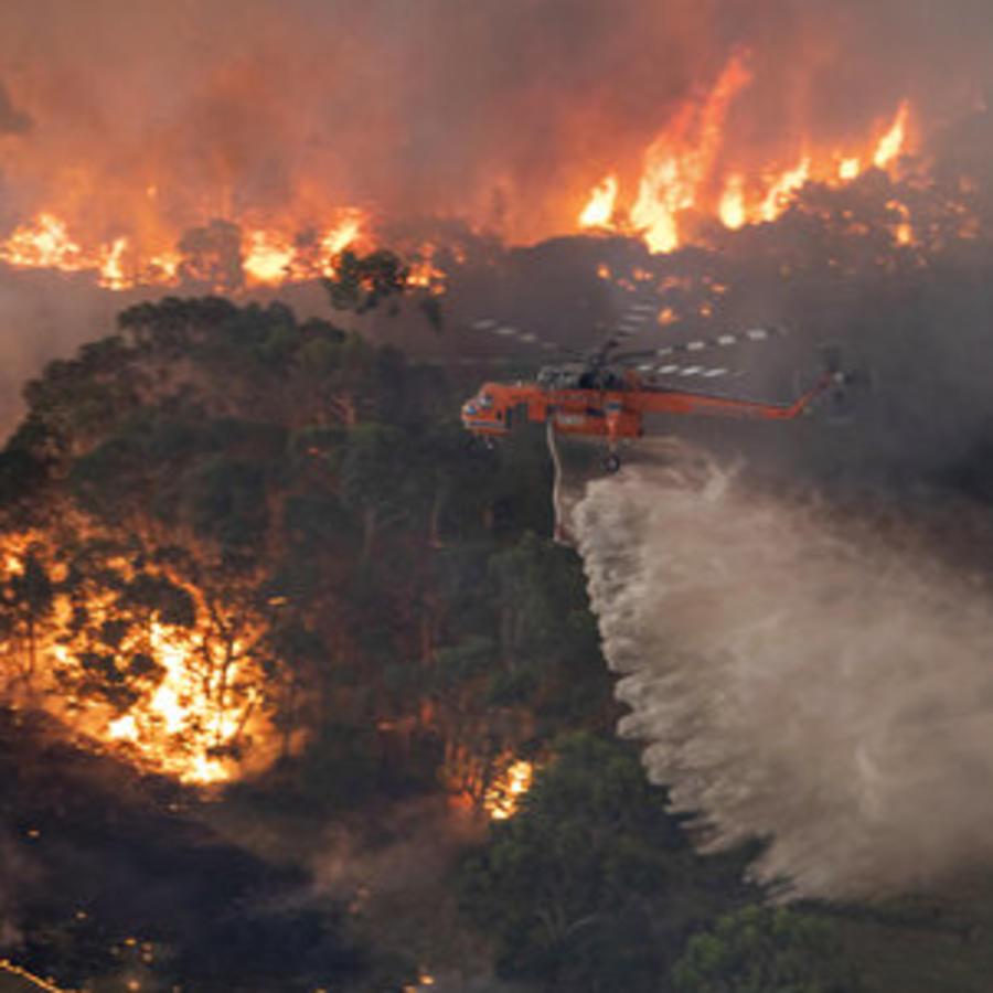 Un helicóptero arroja agua sobre un bosque devastado por un incendio en el estado de Victoria, en Australia.