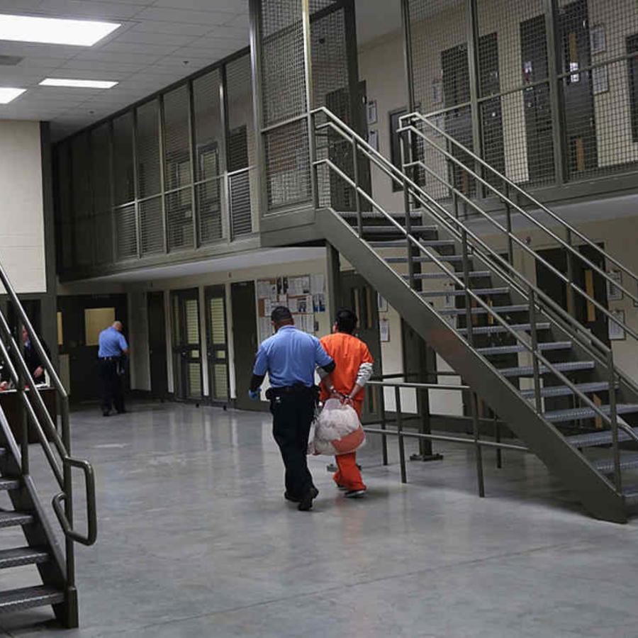 Un guardia escolta a un inmigrante detenido en un centro de detención de ICE.