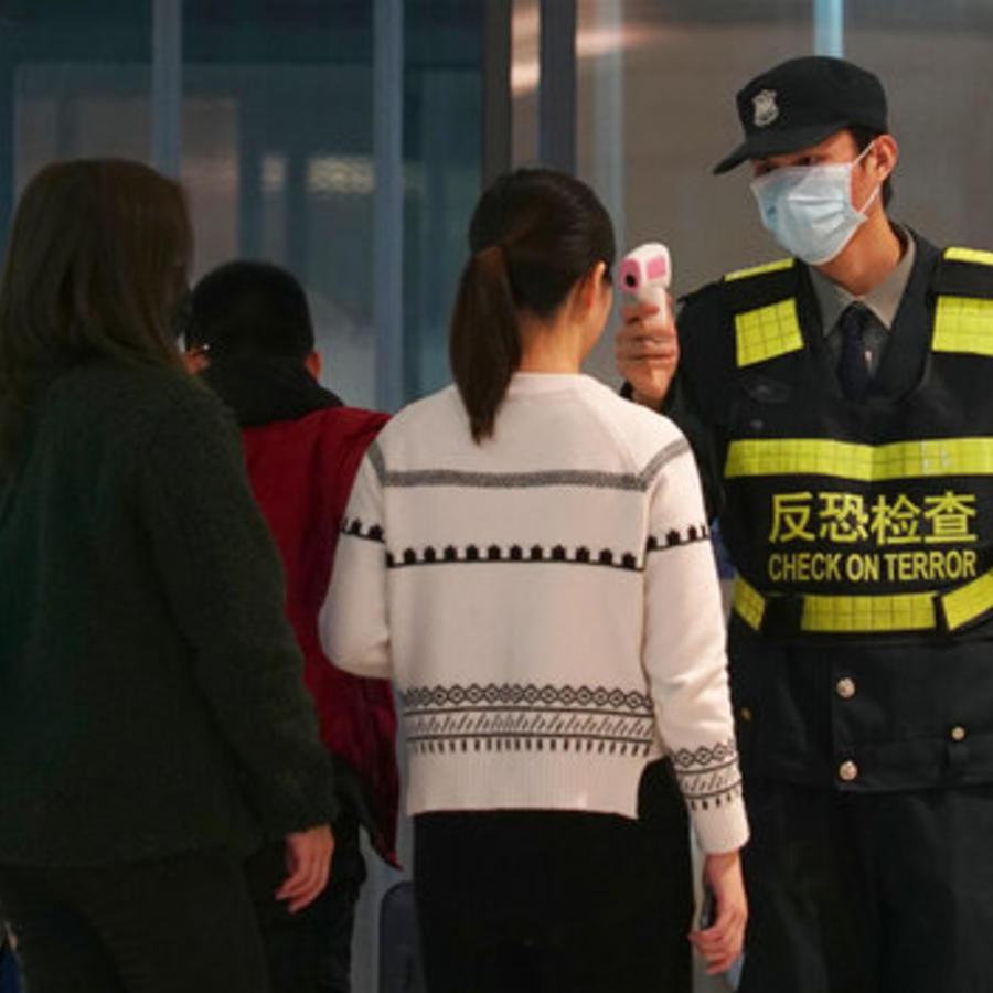Un miembro del personal del aeropuerto utiliza una pistola de temperatura para controlar a las personas que salen del aeropuerto internacional de Wuhan Tianhe en Wuhan, China,