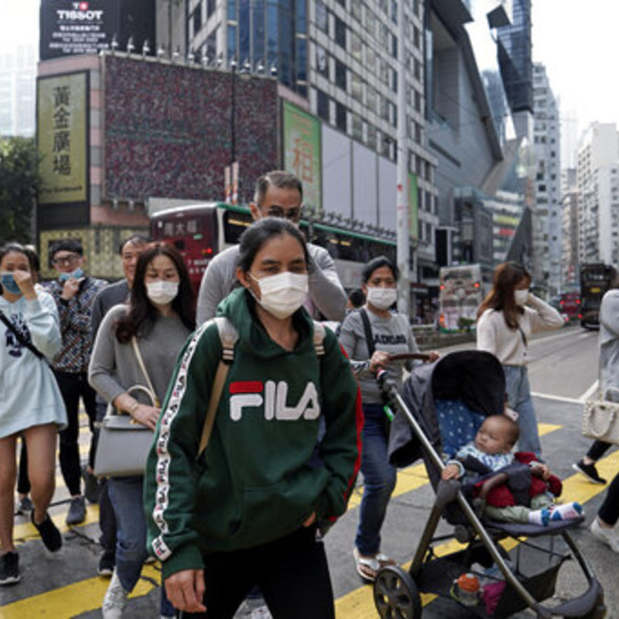 Transeúntes con máscaras protectivas para evitar el contagio del coronavirus chino cruzan este viernes una calle de Hong Kong.