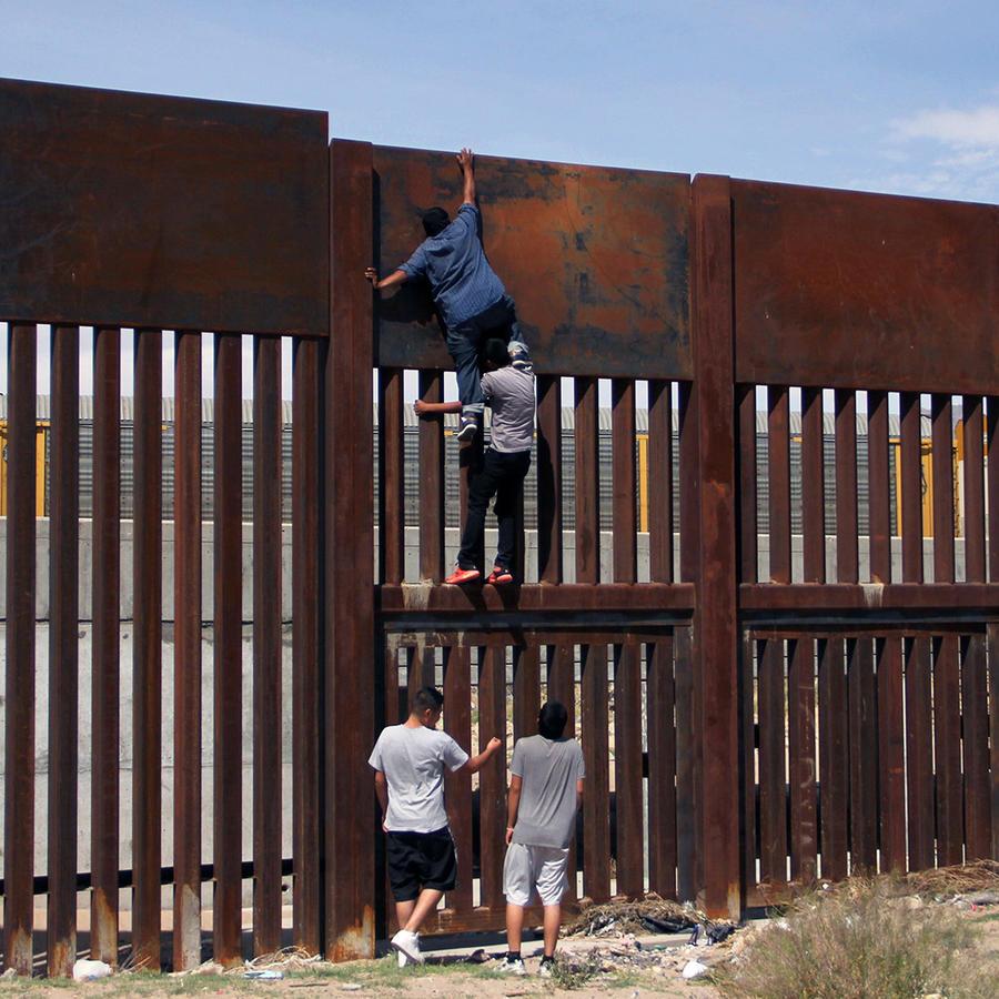 Unos jóvenes mexicanos trepan el muro en Ciudad de Juárez.