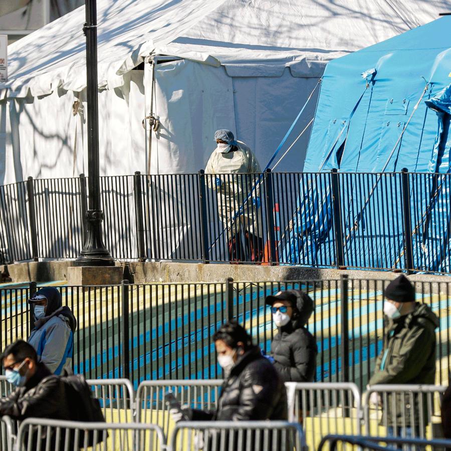 Un trabajador médico observa a una línea de pacientes que esperan la prueba COVID-19 fuera del Centro Hospitalario Elmhurst, en Nueva York.