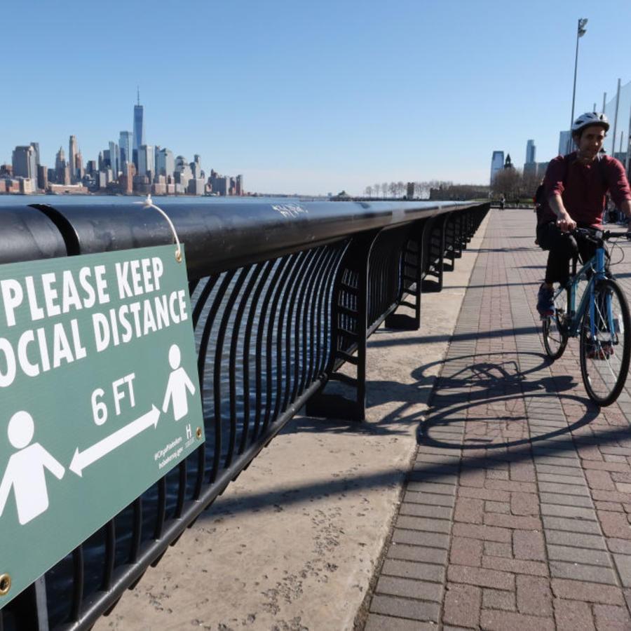Un ciclista pasa junto a un cartel que alienta el distanciamiento social en Hoboken (Nueva Jersey).
