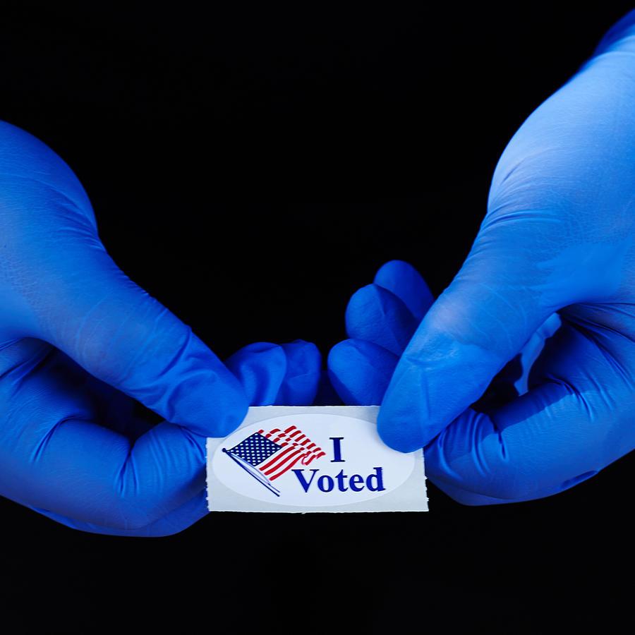 """Un votante sostiene una calcomanía de """"Yo voté"""" usando guantes de látex tras votar en las primarias de Florida, 17 de marzo en Oldsmar, Florida. Los voluntarios encuestados dicen que la participación en persona ha disminuido en la mayoría de los lugares d"""